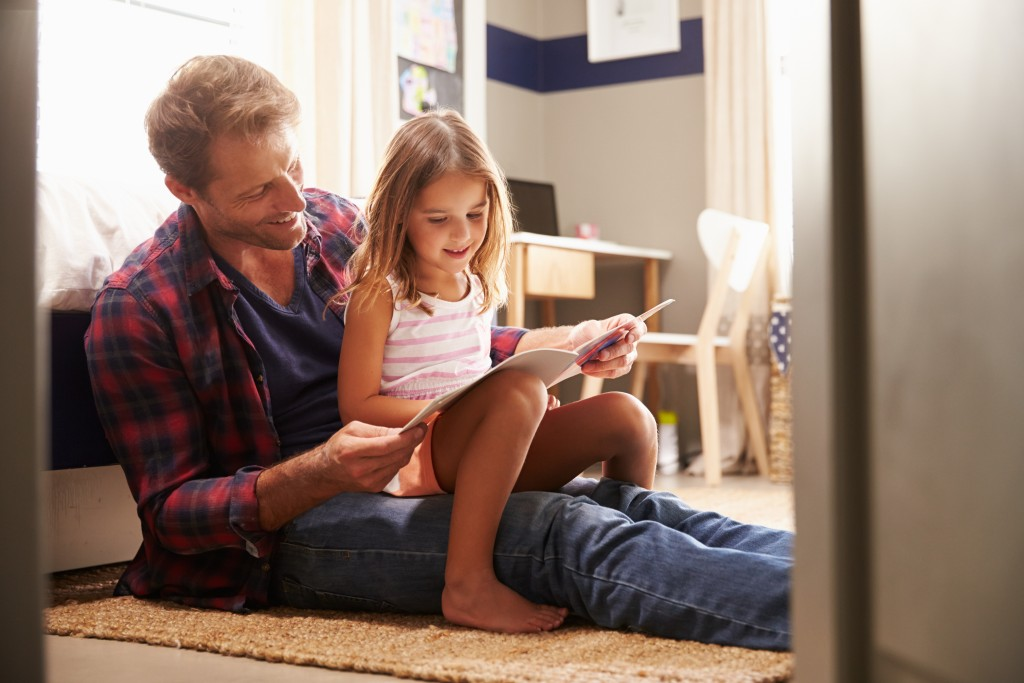 father reading a book with daughter