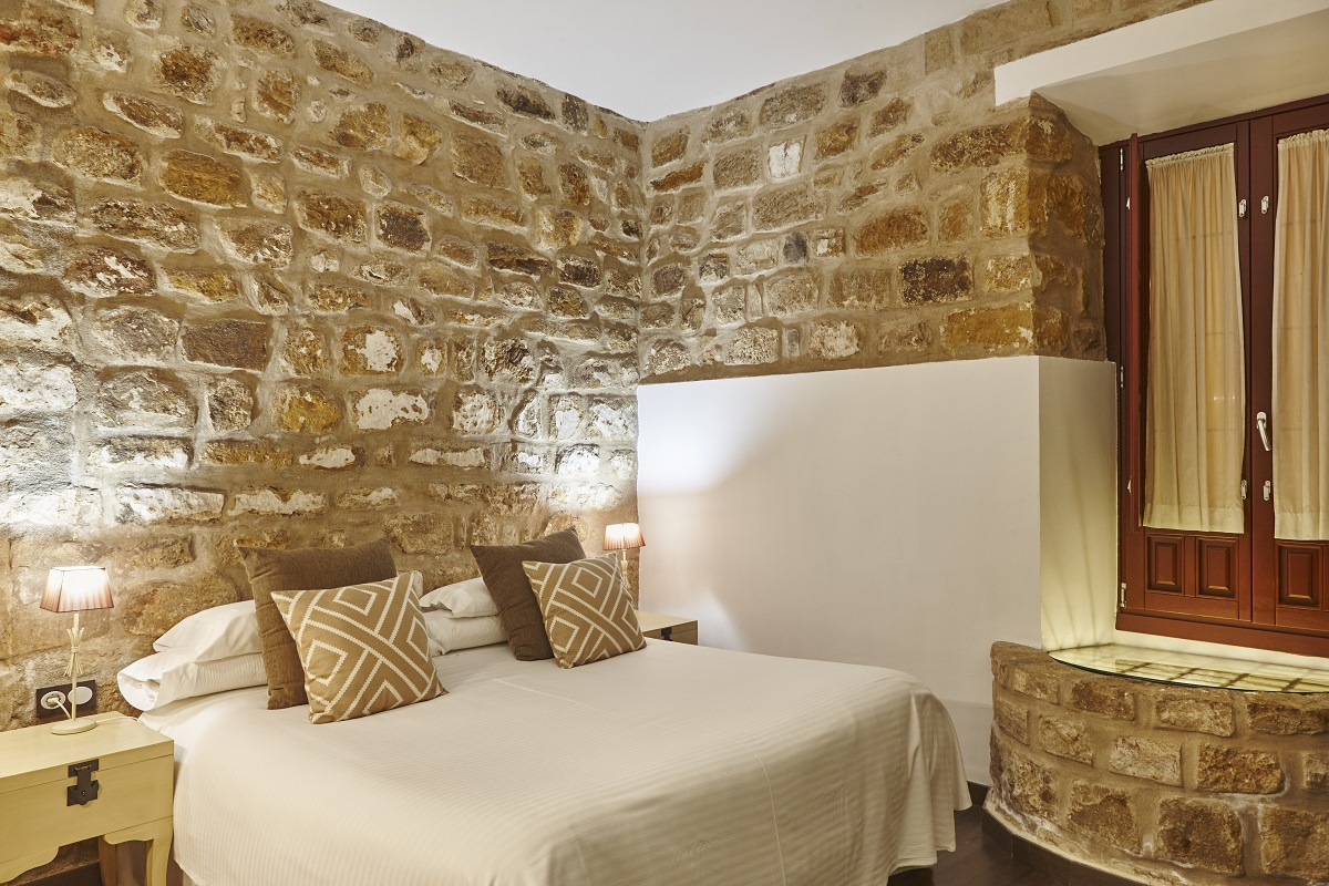 Bedroom with stone walls. Comfortable modern hotel room