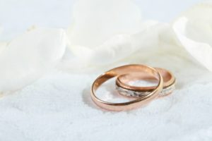 wedding rings surrounded by white petals