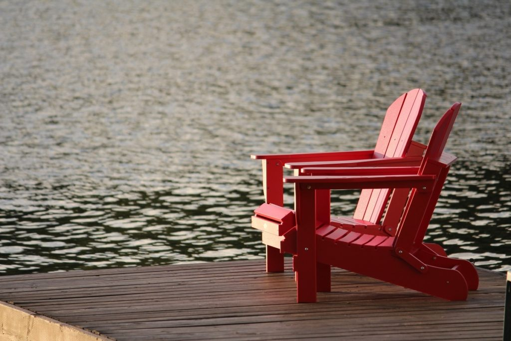 red wooden chairs on a dock