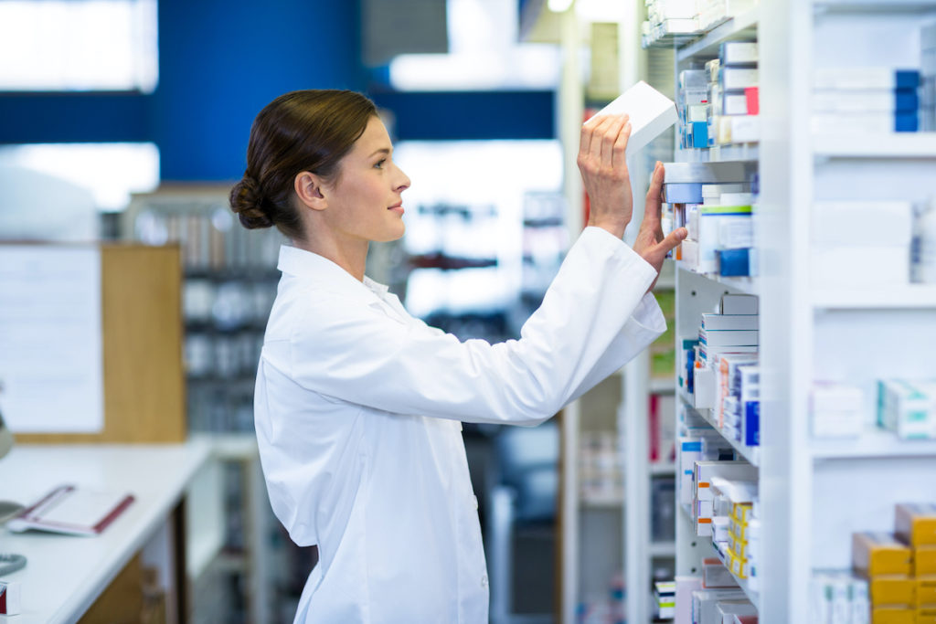 pharmacist pulling something out of the shelf