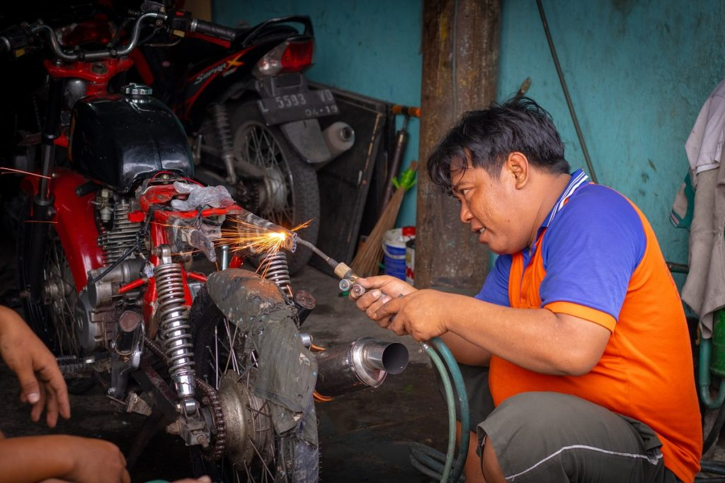 Man repairing motorcycle
