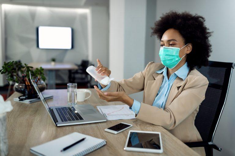woman working wearing facemask applying hand sanitizer