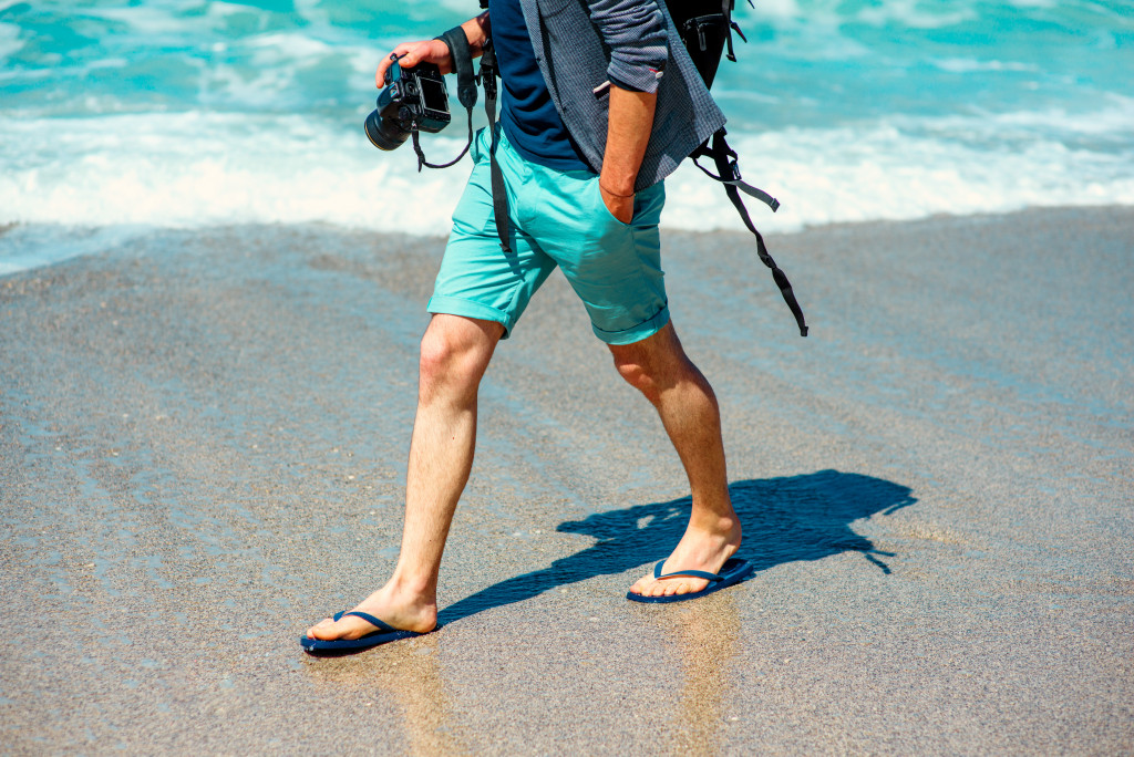 man wearing slippers walking at the beach