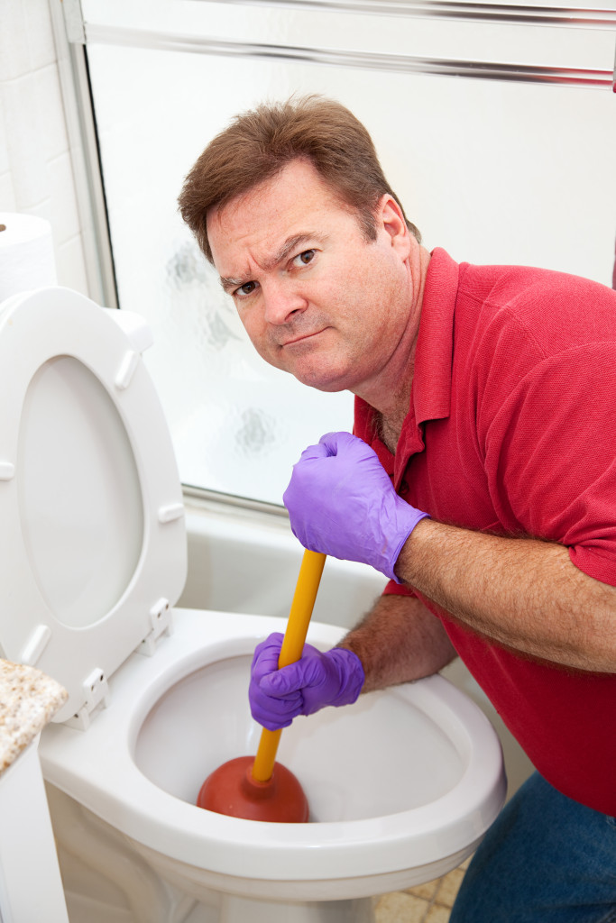 man cleaning a toilet